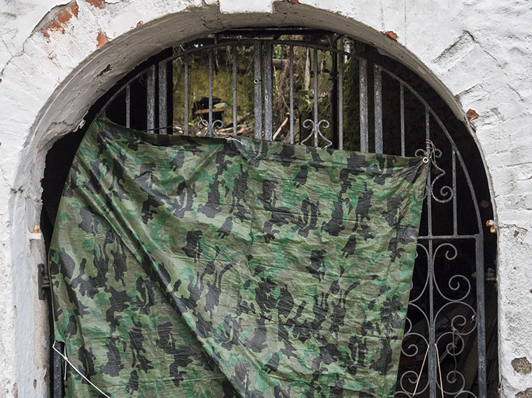 camouflage pattern tarpaulin over gateway to derelict building